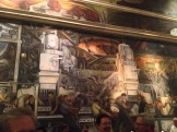 Along the top of two panels (this one and the one on the opposite wall), four women represent coal, coke, iron and stone
